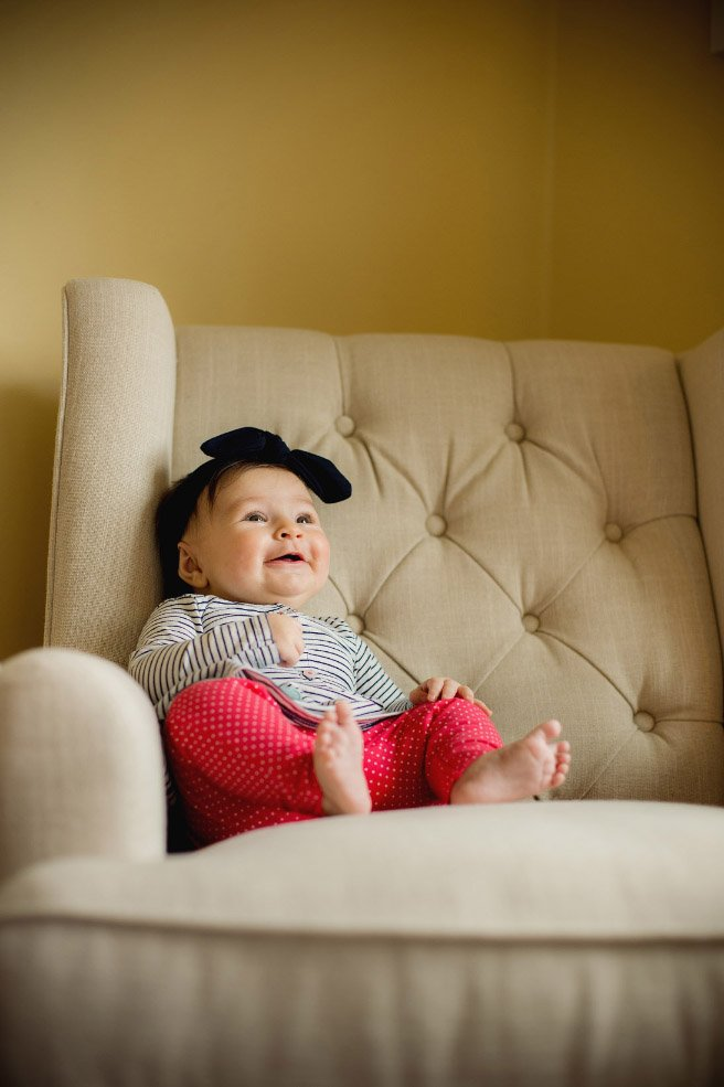 Baby's First Year in Photos - Sitting in armchair smiling at parents